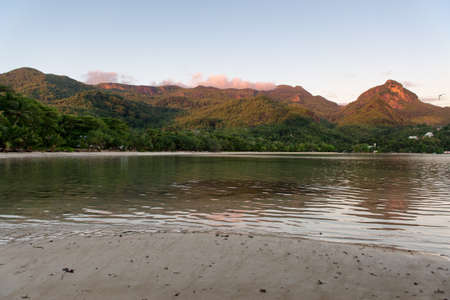 morne: Beautiful Bay Water with Mountains Afar at Morne Blanc in Seychelles Island. Stock Photo