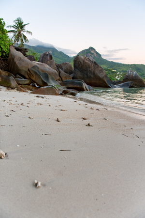 Old Large Rock Formations at the Beach of Mahe Island, Seychelles with White Beach Sand. photo