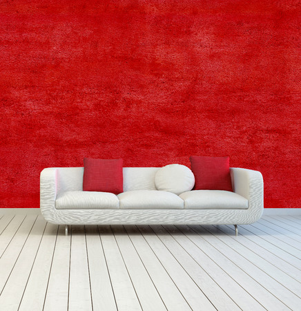 White Sofa with Red and White Pillows on an Empty Room with Red Wall Background and Off White Wooden Floor. photo