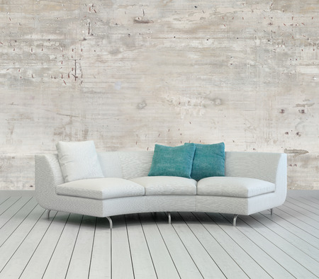Elegant White Couch with White and Green Pillows on an Empty Living Room with Unfinished Concrete Wall Design. photo