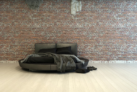 Modern double bed with throws lying over the mattress and pairs of shoes on the floor alongside in a minimalist bedroom with a face brick wall and wooden floor