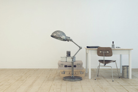 interior: Small simple work area with a table and chair , a standard lamp and vintage suitcases on the floor in a white painted room with wooden floor and copyspace in a modern interior design