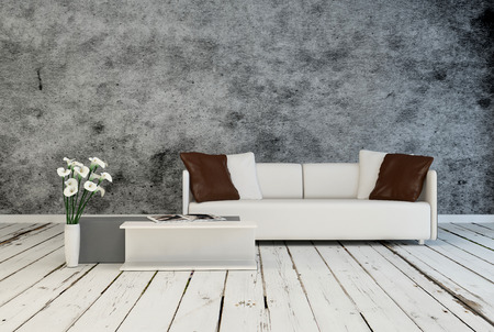 Modern minimalist grey and white living room interior decor with an upholstered couch and low table standing on rustic weathered white painted floorboards against a textured grey wall Stock Photo