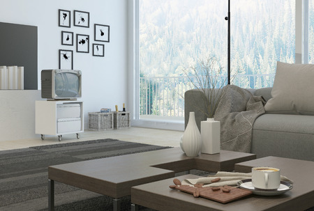 near side: White Coffee cup and decorative vases on wooden table at the architectural living room with television at the side near the wall. Stock Photo