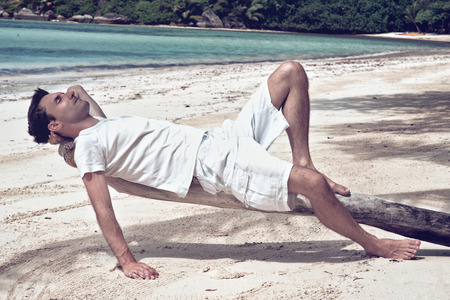lying on back: Young man relaxing on an old tree at the beach lying on his back looking into the sun with closed eyes as he enjoys a hot summer day in the tropics while on vacation Stock Photo