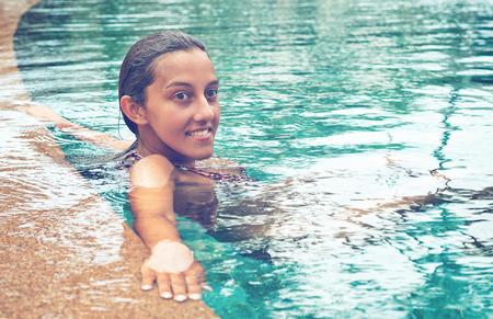 unwinding: Smiling young asian indian woman resting at the swimming pool with arms on the edge. Looking at the right frame