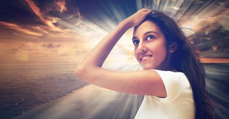 mujer mirando el horizonte: Cierre de la mujer joven sonriente vistiendo camisa blanca, posando con una mano en la frente, en la puesta del sol en el fondo del mar con el Resumen de Iluminación Luz. Foto de archivo