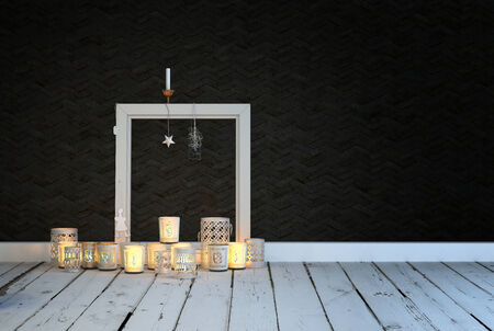 Festive or spiritual background of an arrangement of decorative glowing burning candles on a rustic white painted wooden floor in a room with a black wall and empty picture frame with copyspace photo