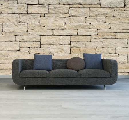 Comfortable grey upholstered sofa with cushions standing on a grey parquet floor against a textured rough stone wall photo