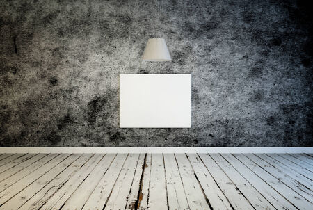 both sides: Blank white canvas for your artwork under a hanging lamp on a textured patterned grey wall over a grunge rustic weathered wooden floor, centered with copyspace on both sides, interior decor or gallery Stock Photo
