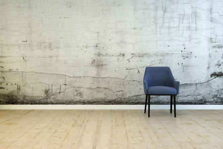 uncarpeted: Single armchair in front of a stained wall with cracked plaster and mildew from damp on a worn wooden parquet floor in a grunge architectural background with copyspace