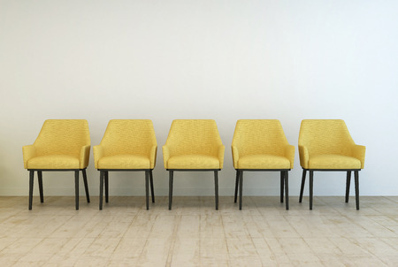 Rij van lege gele stoelen staande op een houten parketvloer tegen een witte muur in een wachtkamer interieur Stockfoto