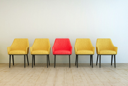 Row of yellow empty chairs aligned against a grey wall of a lobby or a waiting room, with a red one in the middle, concept of making a difference
