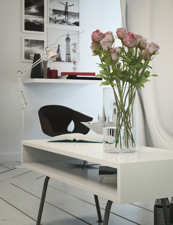 Small office area in a modern apartment with a table, chair and shelving with artwork on the white wall, tiled white floor and a decorative flower arrangement photo