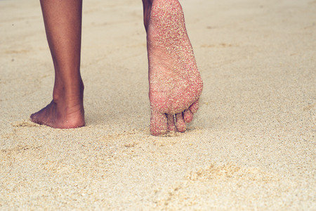 Low angle close up view of the bare feet of an Asian woman exploring a tropical beach walking away across the golden sand