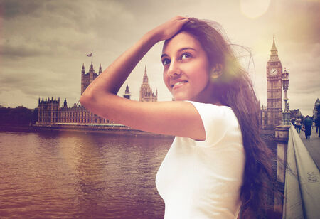 student travel: Long Hair Young Woman in Casual White Shirt Posing Near River Thames with Big Ben in London at the Background. Capturing her with One Hand on the Forehead and Eyes are Looking Up.