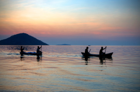 Four men boating in lake Malawi