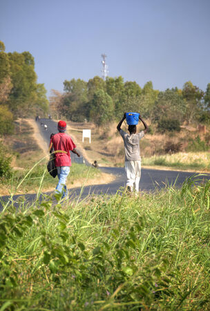 young men: Two young men walking on the road in Malawi