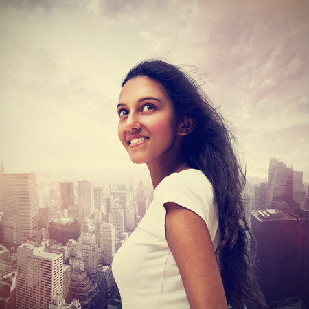 observant: Smiling young Indian woman looking up into the sky against a misty modern cityscape with skyscrapers in a travel and vacation concept Stock Photo