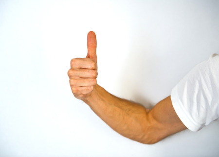 arm extended: Close up view of the hand of a man giving a thumbs up gesture of approval and success with his knuckles towards the camera and arm extended from the side, isolated on white