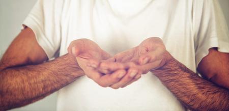 limosna: Hombre que pide, tomar la comunión o la promoción de un objeto frágil en sus vacías las manos ahuecadas en poder frente a su pecho en una camiseta blanca, concepto gesto