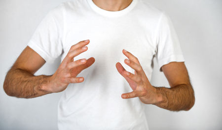 spread around: Man making a hand gesture to clasp a round object with his hands on opposite sides and fingers spread, blank space in between over his white t-shirt