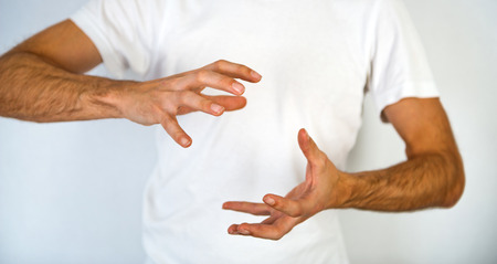 spread around: Close up torso view of a man making a hand gesture to clasp a round object with his hands positioned top and bottom and fingers spread, blank space in between over his white t-shirt