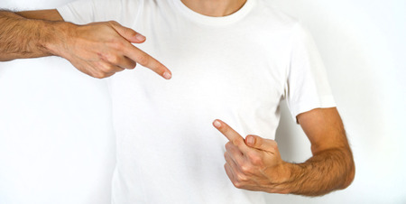inwards: Man pointing inwards with the index finger of both hands from the top and bottom diagonal corner towards blank copyspace in between on his chest in a plain white t-shirt Stock Photo