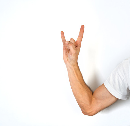 satanist: Close up view of the arm of a man making a horns gesture depicting Satan and the Devil, or heavy metal rock n roll music, isolated on white