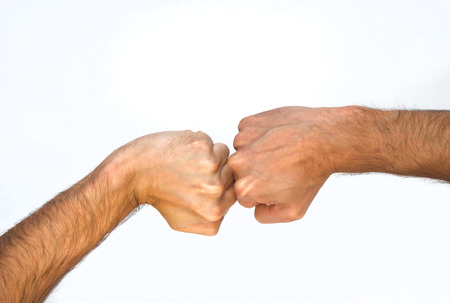 extremity: Two orientations of a man clenching his fist viewed from above, one with a bent wrist and one straight, with the fists touching, close up view of the arm isolated on white