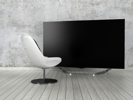 Single modern white comfy chair standing on a white painted parquet floor in front of a large flat screen TV in a minimalist home