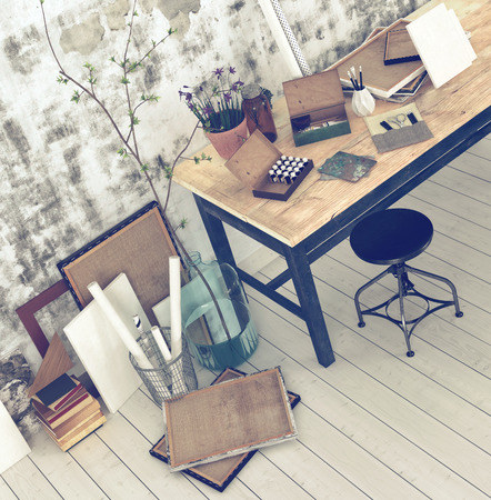 stool: Interior of an artist or designer studio with blank canvasses, picture frames and supplies on a simple black wood work table with a stool against an abstract patterned grey wall Stock Photo