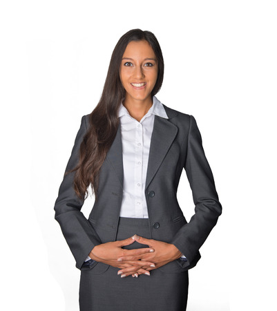 demure: Welcoming secretary or businesswoman standing with her hands clasped over her stomach looking at the camera with a bright friendly smile, isolated on white Stock Photo