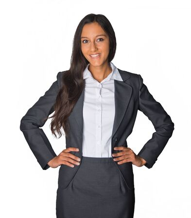 assertive: Attractive confident Indian business executive in a stylish suit standing with her hands on her hips smiling at the camera, isolated on white