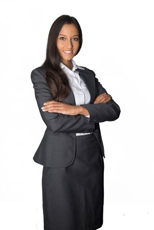 stance: Attractive confident young Indian manageress in a stylish business suit standing with folded arms smiling at the camera, isolated on white