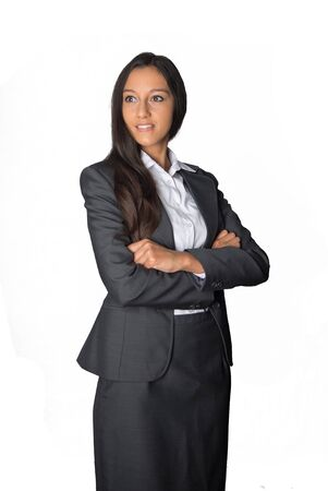looking away from camera: Smiling young Asian businesswoman in a stylish grey suit standing with folded arms looking away from camera, conceptual of authority and leadership, isolated on white Stock Photo
