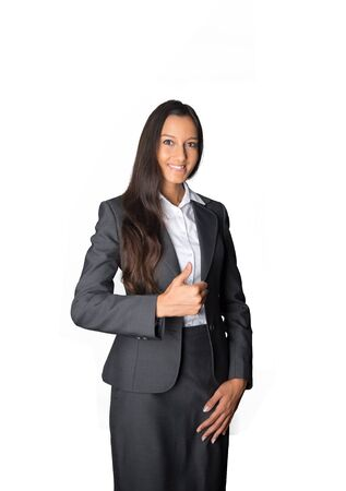 endorsement: Smart attractive young Indian businesswoman giving a thumbs up of approval and success as she stands smiling at the camera, isolated on white Stock Photo
