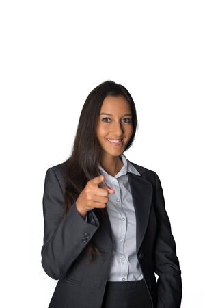 identifying: Young Indian businesswoman in a stylish jacket standing pointing at the camera conceptual of choosing, identifying, showing or a chat show host, isolated on white