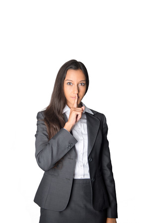 shush: Serious young businesswoman asking for silence holding her finger to her lips in a shushing gesture, isolated on white Stock Photo