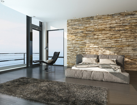 Modern sunny bedroom overlooking the ocean with a balcony, view window, contemporary double bed with padded upholstered headboard and foot board against a rough stone texture feature wall Stockfoto