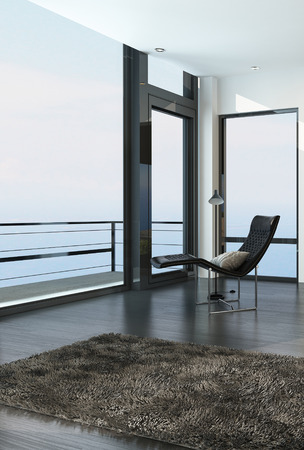balcony design: Chair overlooking the ocean through a floor-to-ceiling glass wall in a modern coastal living room with a balcony and door with a beige rug on the floor Stock Photo