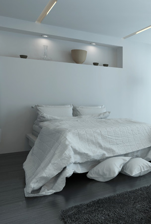 Double bed with large duvet and extra pillows on the floor in a modern white bedroom interior illuminated by recessed down lights in an alcove photo