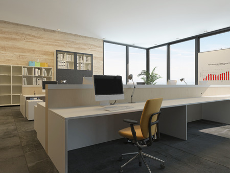 Modern office interior with multiple open-plan work stations at long desks in a spacious airy room with floor-to-ceiling glass windows on two walls