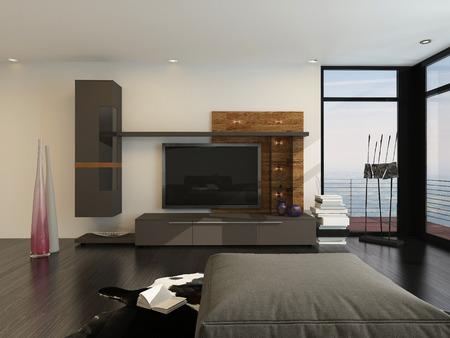 Entertainment room interior with a large flat screen TV and speakers on a wall alongside floor-to-ceiling glass view windows with a comfy ottoman in the foreground