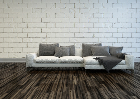 Rustic living room interior with a large white sofa with grey cushions on a bare wooden parquet floor against a white painted rough brick wall