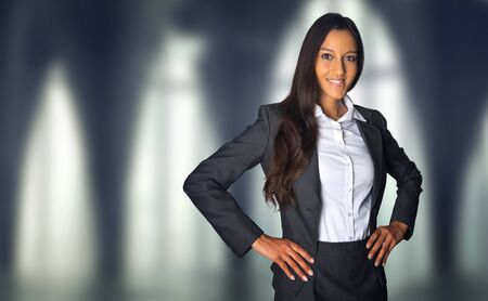 managerial: Successful attractive ambitious Indian businesswoman standing with her hands on her hips in a corporate building smiling at the camera