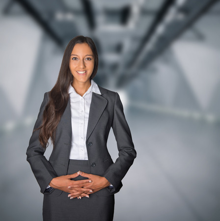 demure: Demure businesswoman with a welcoming smile standing in the entrance to a corporate building with her hands clasped over her stomach waiting to welcome guests Stock Photo