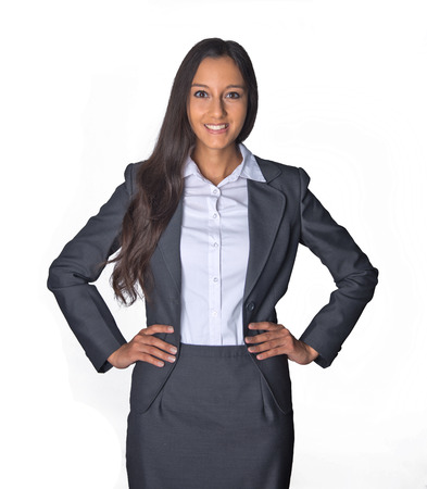 hands on hips: Attractive confident Indian business executive in a stylish suit standing with her hands on her hips smiling at the camera, isolated on white