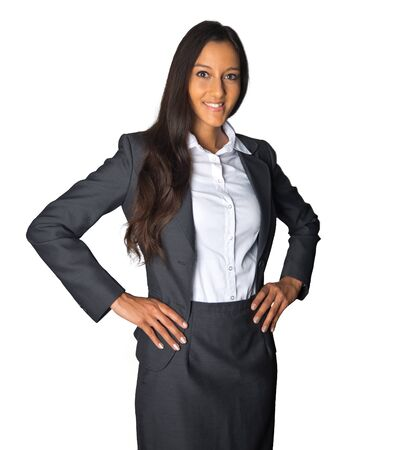 achiever: Smiling successful young Indian businesswoman in a fashionable suit standing with her hands on her hips looking at the camera, on white