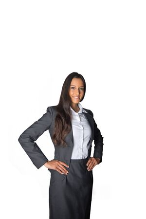 authoritative: Authoritative young businesswoman standing watching the camera at an angle with her hands on her hips and smile of satisfaction, isolated on white Stock Photo